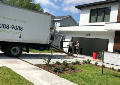 a group of movers offloading a truck in a residential home