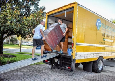 This is an image of 2 men moving a dresser into a Teleport Moving truck.
