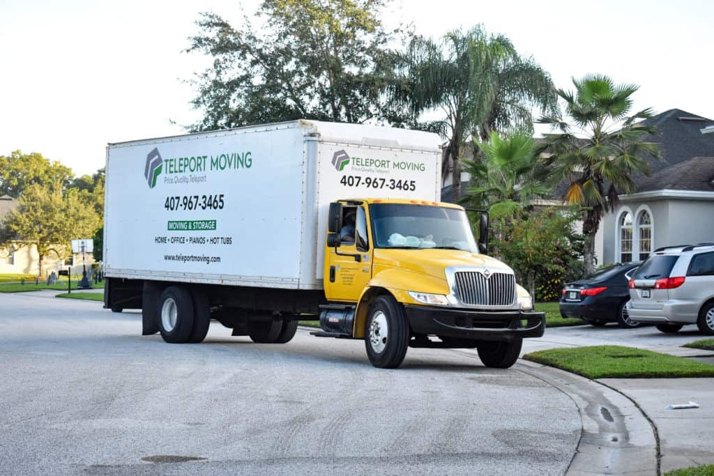 This is an image of a white Teleport Moving truck parked on a culdesac.