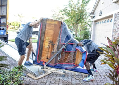 This is an image of Teleport Moving employees unloading a piano.