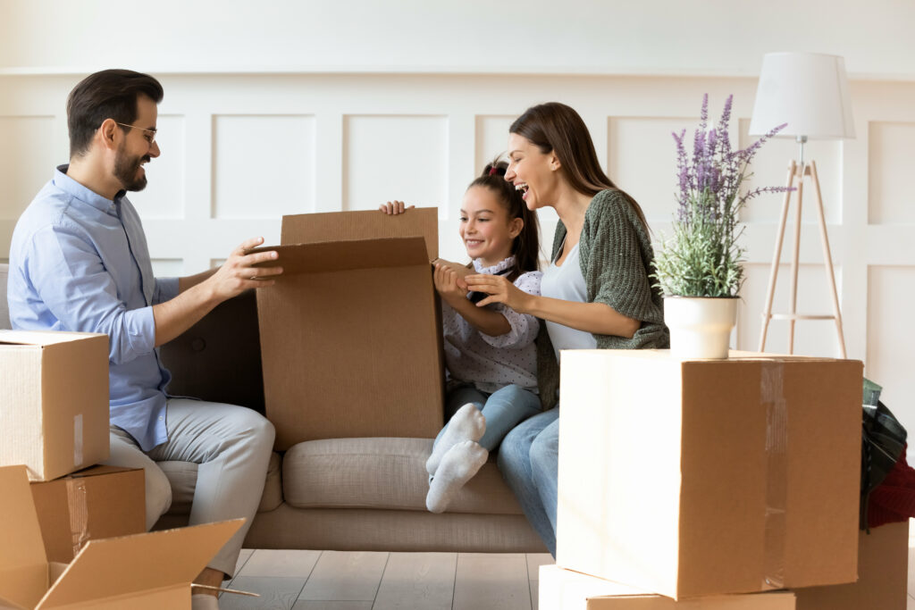 Adorable daughter helping parents with cardboard boxes on moving day, happy family with child sitting on couch, unpacking belongings in modern living room, relocation and mortgage concept